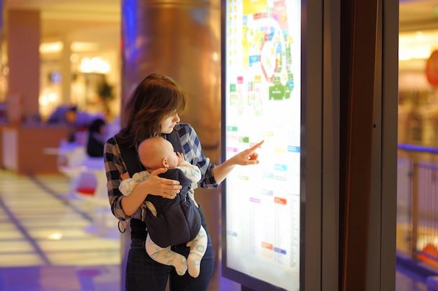 ショッピングモールで彼女の小さな赤ちゃんを持つ若い女性