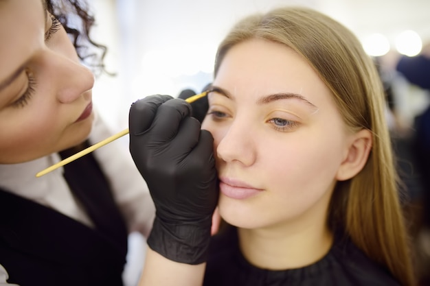美容師がブラシで眉を塗ります。