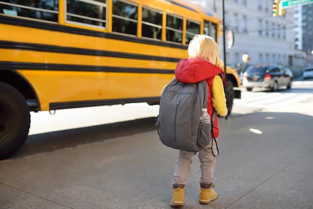 黄色のスクールバスの近くのランドセルと生徒