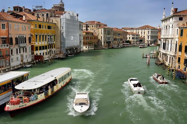 Вид на гранд-канал венеции с лодки, вапаретто и моторные лодки