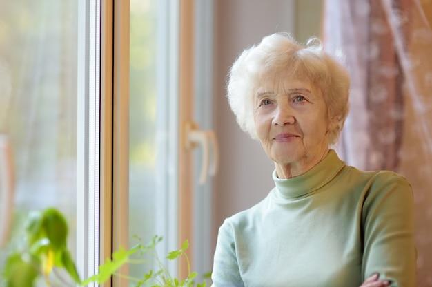 白い巻き毛の美しい笑顔の年配の女性の肖像画。老婦人は家の窓のそばに立っています。