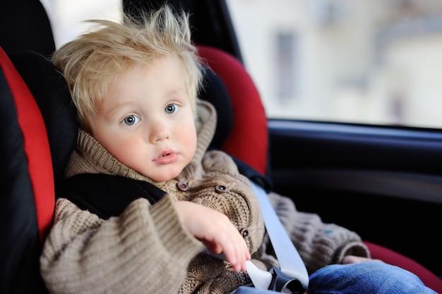 車の座席に座っているかなり幼児男の子の肖像画。子供の交通安全