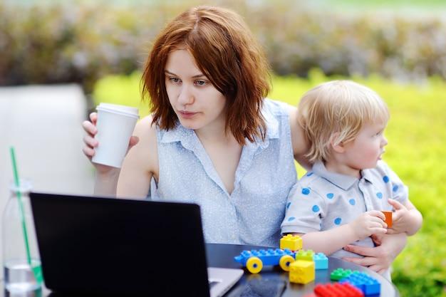 若い母親は彼女のラップトップを働いて、彼女の悲しい幼児の息子を保持