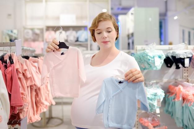 Молодая беременная женщина выбирает розовую или голубую одежду в магазине для новорожденных