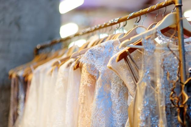 いくつかの美しいウェディングドレスがハンガーについています。花嫁やブライドメイドの服