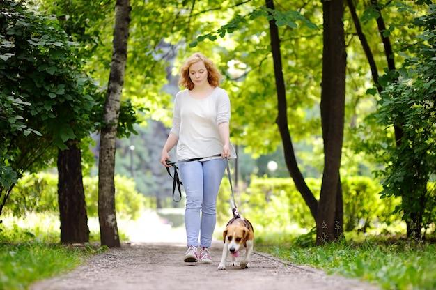 夏の公園でビーグル犬を持つ若い美しい女性。彼女の国内ペットとの愛情のある女性の所有者