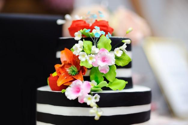 白い砂糖の花で飾られた金のウエディングケーキ。結婚披露宴の甘いテーブル