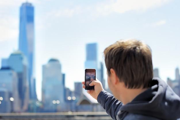 彼のスマートフォンを使用して高層ビルの携帯写真を撮る中年観光客