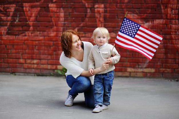 アメリカの国旗を保持している彼女の幼児の息子を持つ幸せな若い女。独立記念日のコンセプトです。