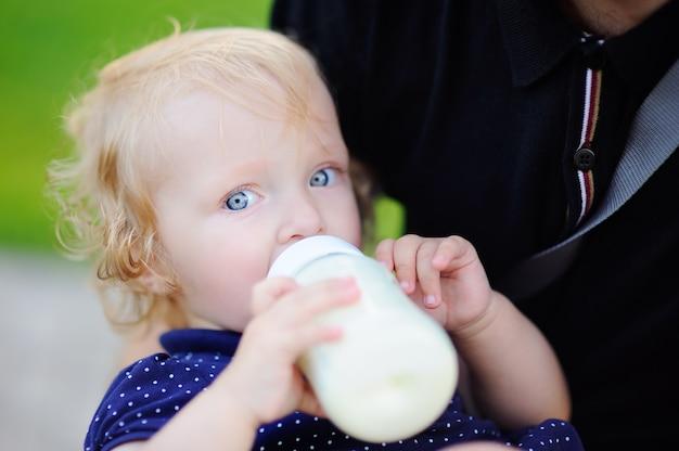 愛らしい幼児の女の子が父の手でボトルから牛乳を飲む