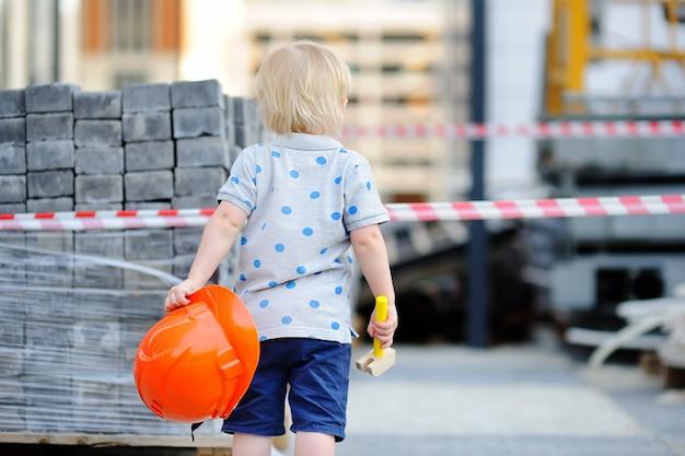 Портрет милый маленький строитель с каски и молот на открытом воздухе