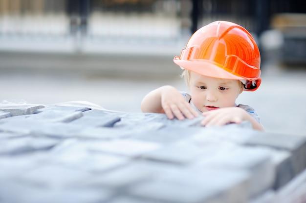 Портрет милый маленький строитель в каски, работающих на открытом воздухе