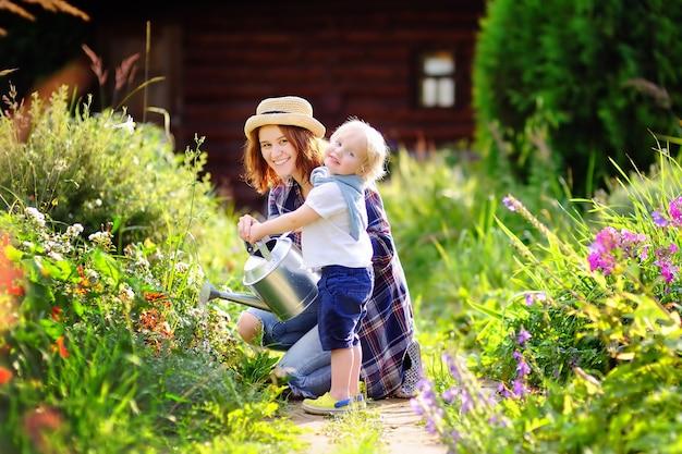 かわいい幼児男の子と彼の若い母親の夏の晴れた日に庭の植物に水をまく
