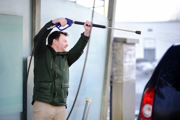 Мужчина среднего возраста моет машину на автомойке. чистая машина