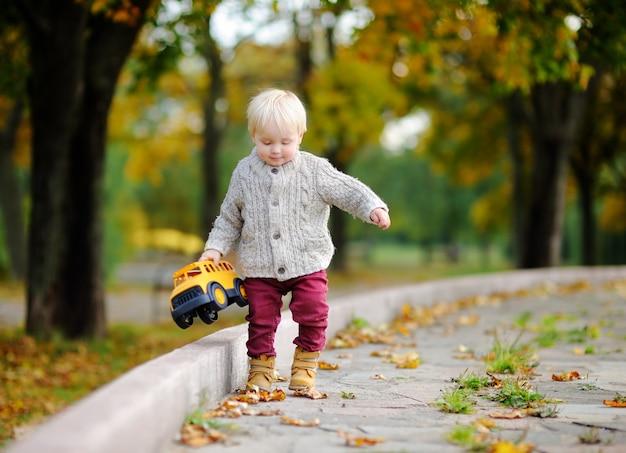 幼児が秋の公園で楽しんでいます。屋外のおもちゃの車で遊ぶ少年