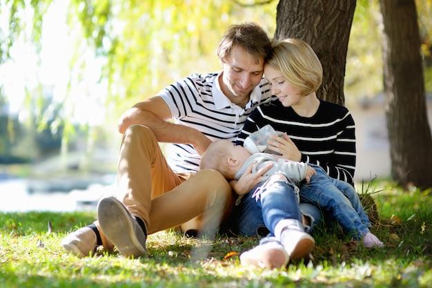 幸せな親子関係:日当たりの良い公園で甘い女の赤ちゃんを持つ若い親