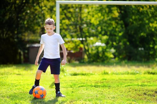 楽しんで晴れた夏の日にサッカーの試合をしている少年