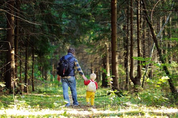 Отец и его малыш сын, прогулки во время походов в осеннем лесу на закате