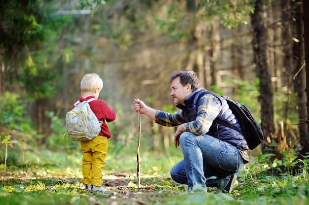 父と彼の幼児の息子が夕暮れ時の秋の森でのハイキング活動中に歩いて
