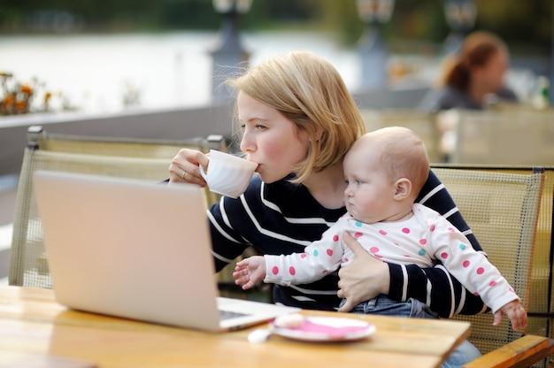 彼女の愛らしい女の赤ちゃんが働いているか、屋外カフェで彼女のラップトップで勉強している若い母親
