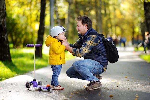 秋の公園で幸せな家族。彼の幼い息子が彼のヘルメットをかぶるのを助ける中年父親。スクーターに乗るアクティブな幼児男の子。子どもの安全