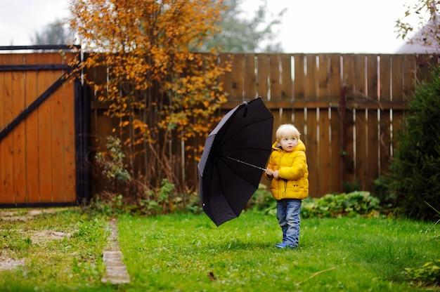 雨の曇りの秋の天気で歩く少年。雨の中で大きな黒い傘を持つ子供。秋の野外活動