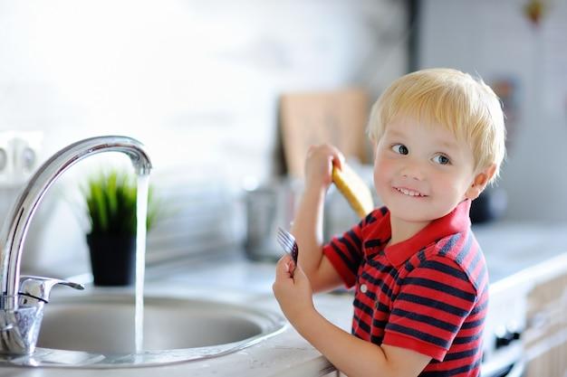 かわいい幼児男の子が家庭の台所で皿洗いをします。両親が家事を手伝って楽しんでいる子供。