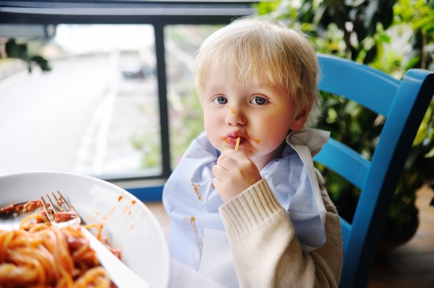 Милый малыш мальчик ест макароны в итальянском ресторане в помещении. здоровая / нездоровая пища для маленьких детей