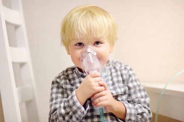 吸入器のマスクによるかわいい男の子吸入療法。呼吸器の問題や喘息の小さな子供の画像を閉じます。明確な酸素マスクを持つ病気の男の子。