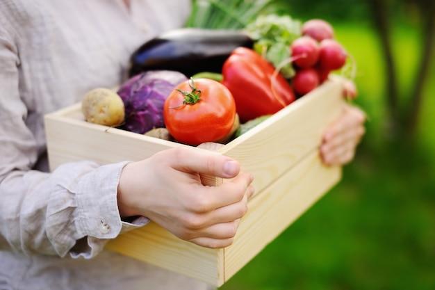 Женщина садовник держит деревянный ящик со свежими органическими овощами с фермы