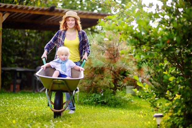 暖かい晴れた日に、家庭菜園で母によって押す手押し車で楽しんで愛らしい幼児男の子。夏の子供のためのアクティブアウトドアゲーム。