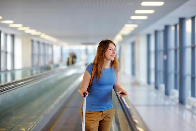 空港でスーツケースを持つ若い女