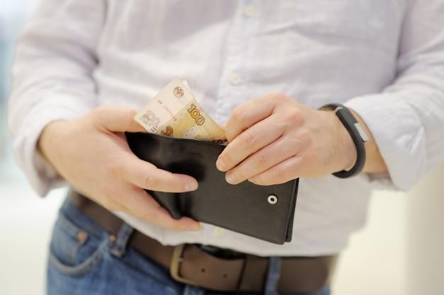 Мужчина держит кошелек с русскими бумажными деньгами (рубли)