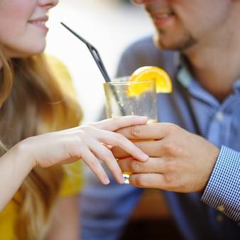 Молодая влюбленная пара держит стакан апельсинового сока