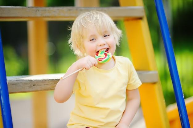 楽しんで、屋外の遊び場で大きなロリポップを食べる小さな男の子