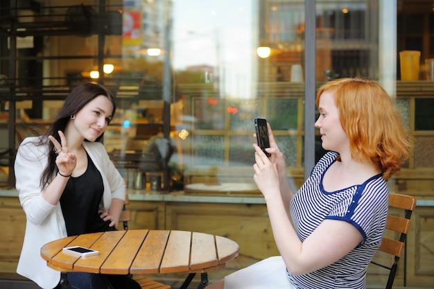 屋外カフェで彼女の友人(携帯に焦点を当てる)の写真を撮る若い女性