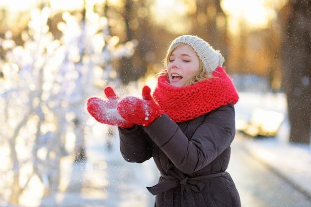 冬で楽しんでいる若い美しい女性の屋外のポートレート