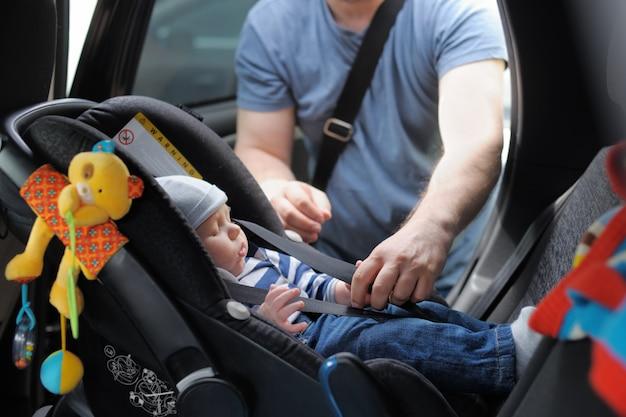 父は幼い息子を車の座席に固定します。