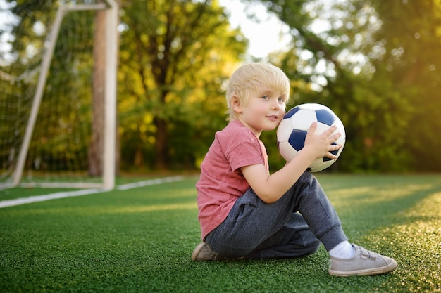 Маленький мальчик, с удовольствием играют в футбол / футбол на летний день. активная игра на свежем воздухе / спорт для детей.