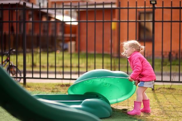 屋外の遊び場で楽しんでかわいい女の子