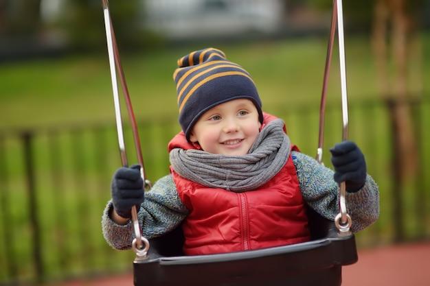 屋外の遊び場で楽しんでかわいい男の子。スイングの子