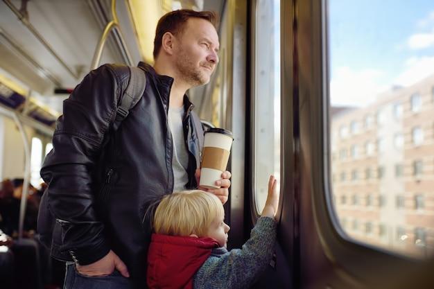 中年の男性と彼の幼い息子はニューヨークの地下鉄で車の窓の外を見ています。
