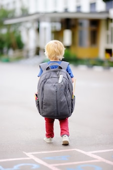 学校のコンセプトに戻る彼のバックパックを持つ若い学生