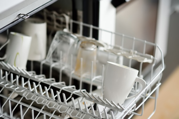 Открытая посудомоечная машина с грязной посудой. крупный план.