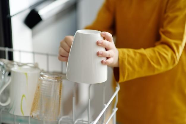 子供が家庭の食器洗い機に汚れた食器を置きます。閉じる。