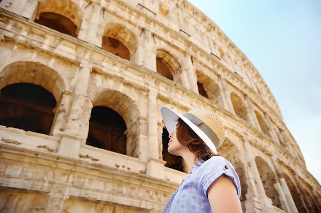 Молодая женщина путешественник, глядя на знаменитый колизей в риме.