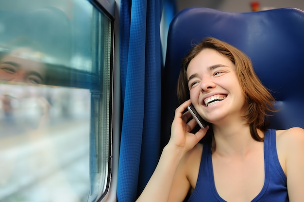 Портрет красивой девушки разговаривает по телефону в вагоне поезда