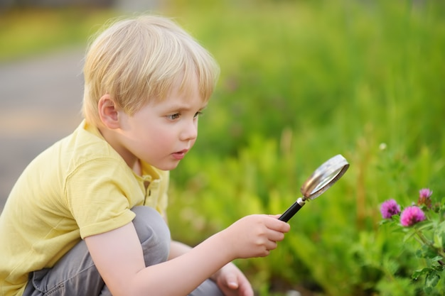 Очаровательный малыш исследует природу с увеличительным стеклом