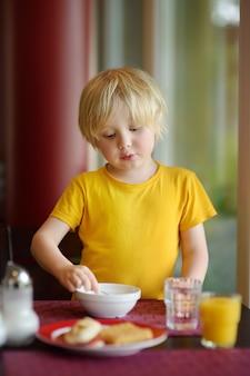 ホテルのレストランで健康的な朝食を食べる小さな男の子。家でおいしい食事。