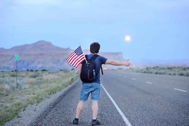 Турист среднего возраста с американским флагом в рюкзаке автостопом по пустынной дороге